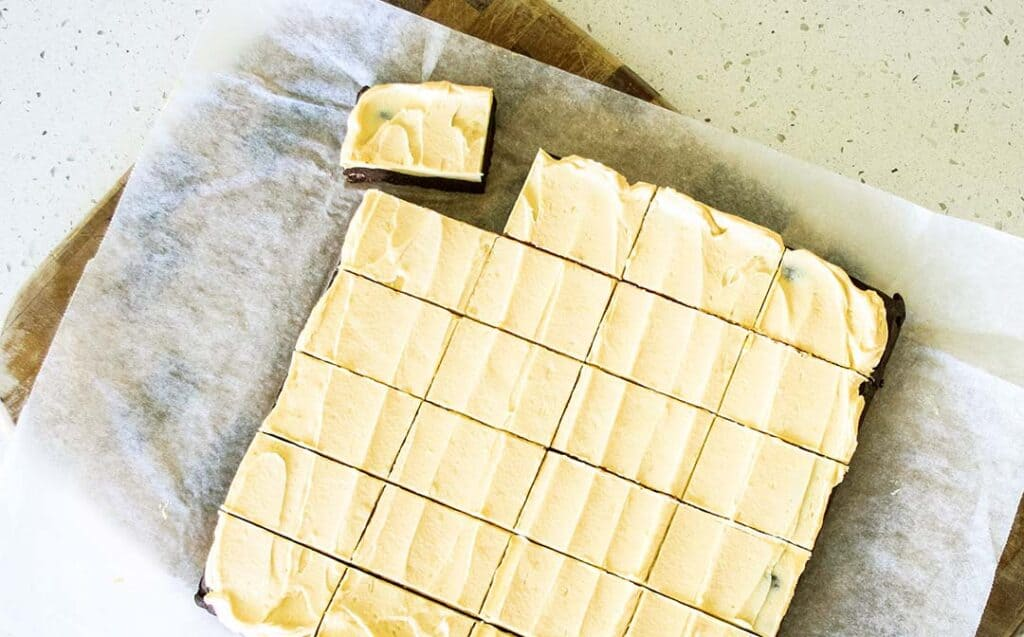 A batch of frosted brownies cut into squares on a baking paper lined cutting board