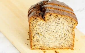 close up image of a slice of banana bread on a wooden board