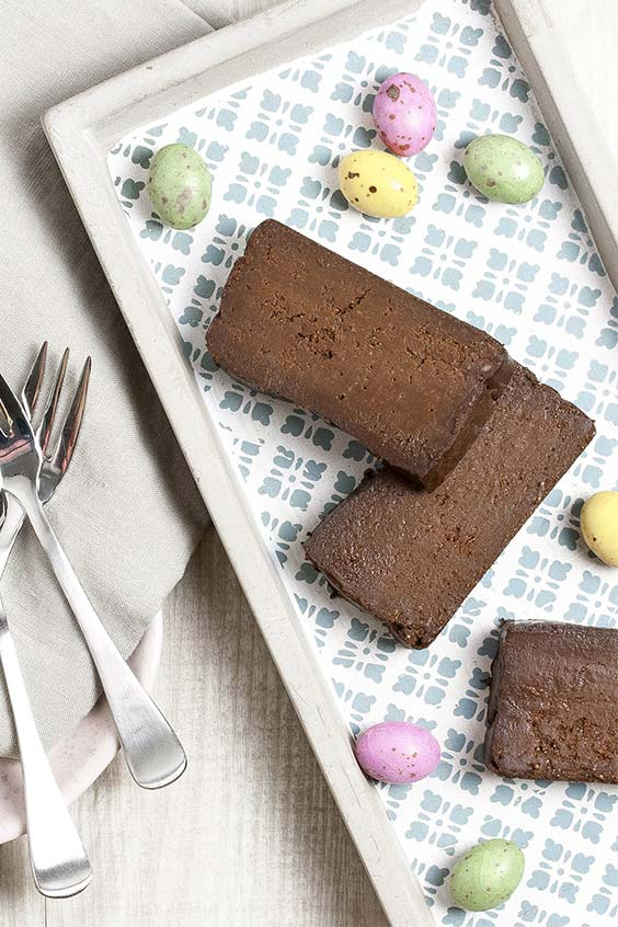 a patterned tray with pieces of chocolate cake and speckled Easter eggs