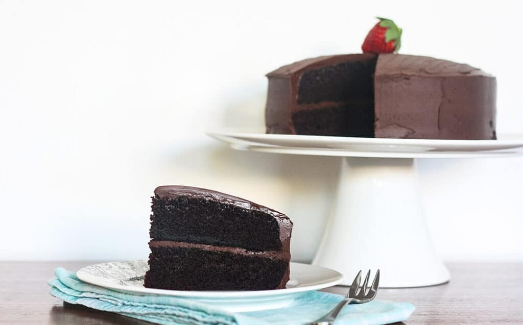 a piece of steam oven chocolate cake in front of the cake on a white stand