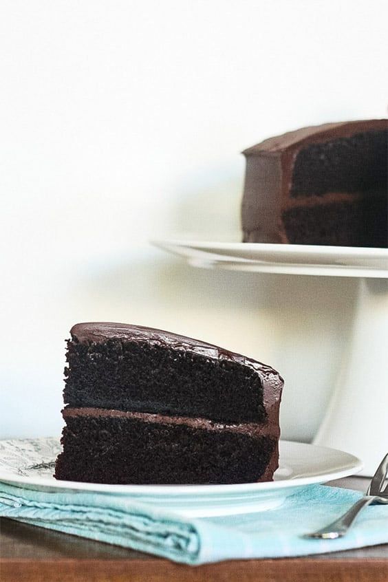 a wedge of frosted chocolate layer cake on a white plate and a fork on a patterned napkin