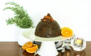 a Christmas pudding garnished with fruit on a white cake stand surrounded by citrus and decorations