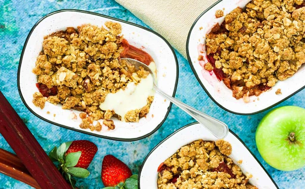 individual enamel dishes filled with red fruit and crumble topping