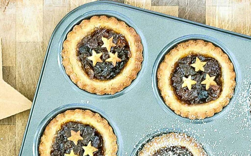 a few fruit mince pies with scalloped pastry and pastry stars garnishing the filling