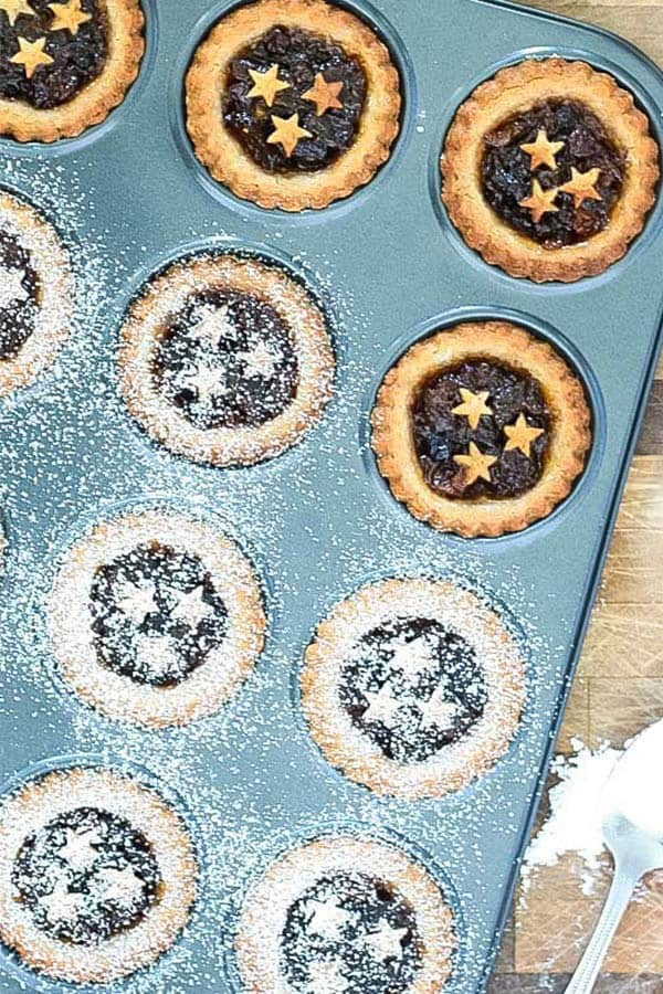 a muffin tray with pies decorated with pastry stars, some sprinkled with icing sugar