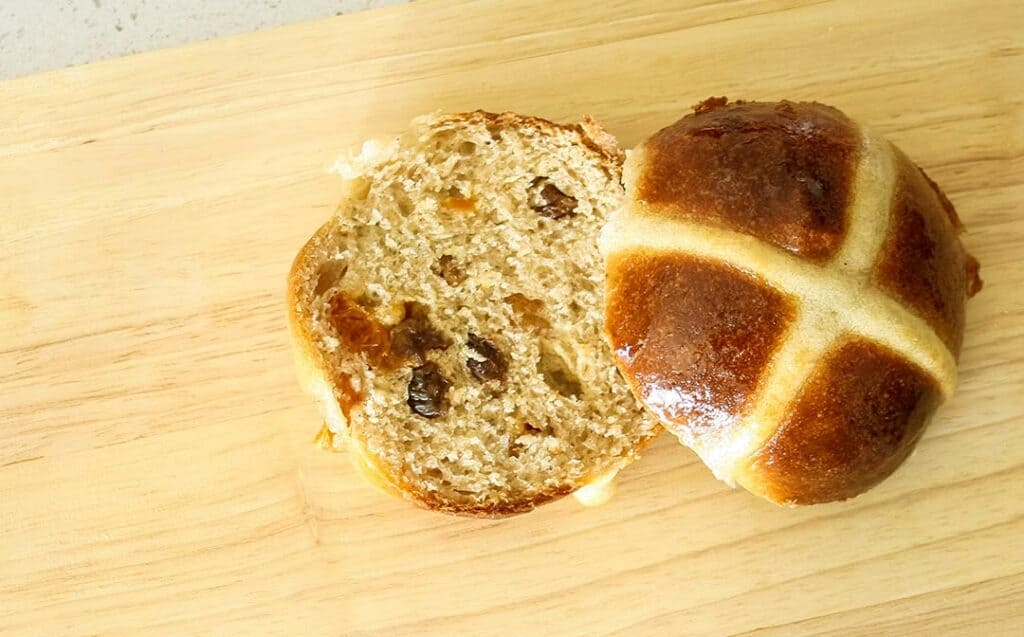 a halved hot cross bun showing the fruit inside on a wooden cutting board