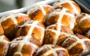 a close up image of golden brown glazed hot cross buns in a baking tin