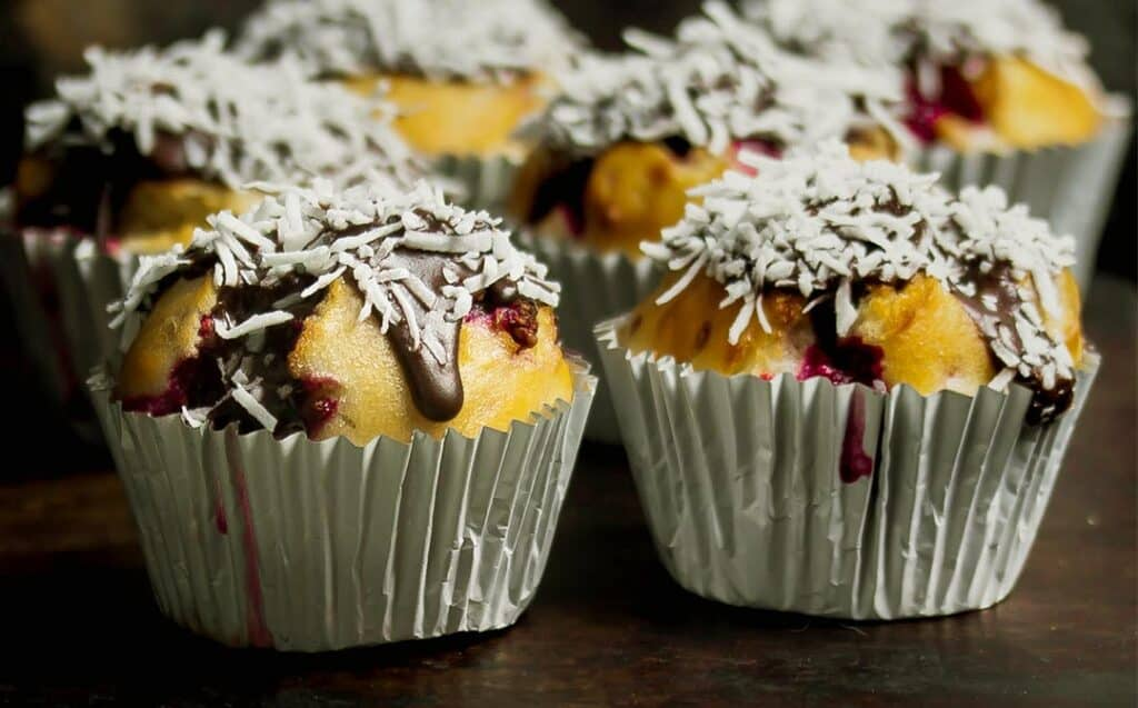 zoomed in image of two muffins of a batch of raspberry Lamington muffins