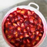 a white baking dish on a grey teatowel filled with roasted red plums