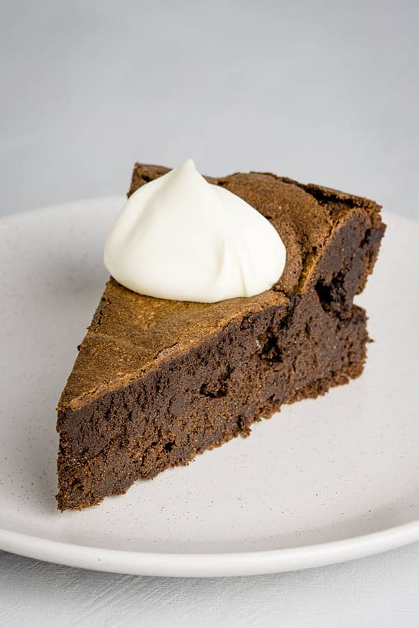 A piece of chocolate cake on a plate with a dollop of cream on top