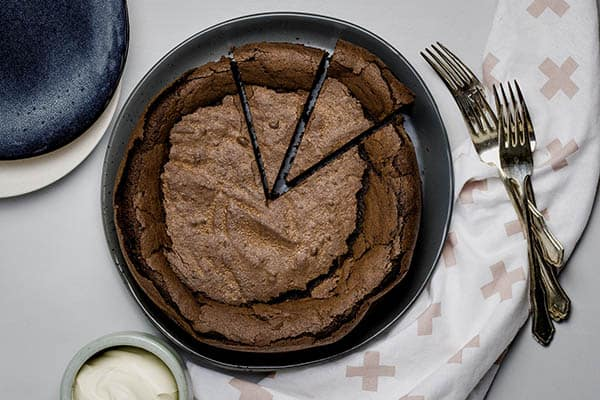 a round chocolate cake with two cut pieces on a dark plate