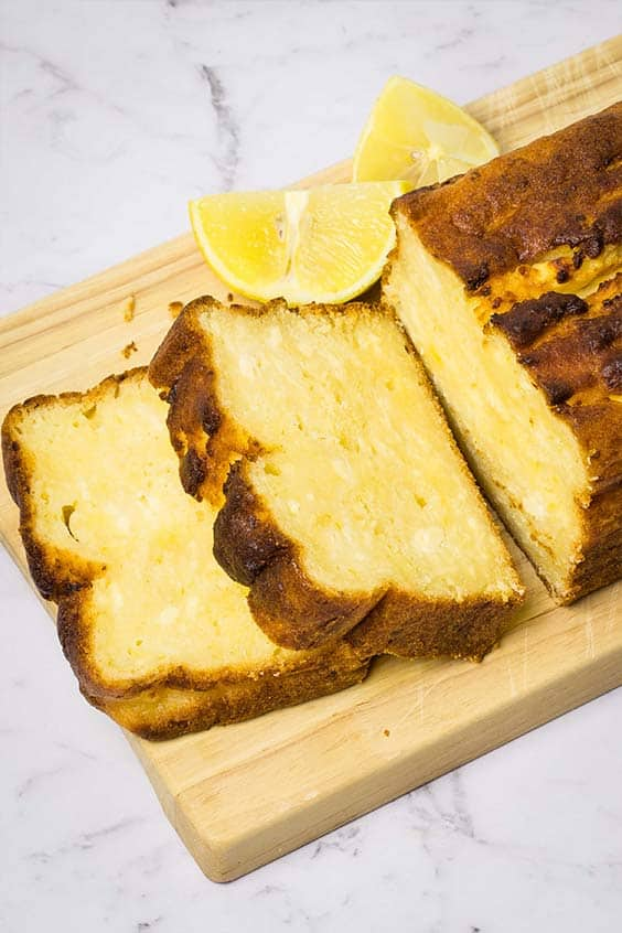 lemon ricotta cake, on a wooden board with two slices cut from the end of the loaf