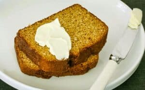 zoomed in image of two thick slices of pumpkin bread with a blob of cream cheese on top and a knife beside them on a white plate