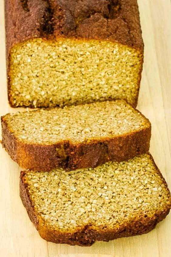 a loaf of golden brown bread with two thick slices cut from the end, on a wooden cutting board
