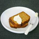 a curved white plate with two thick slices of pumpkin bread with a blob of cream cheese on top and a knife beside them