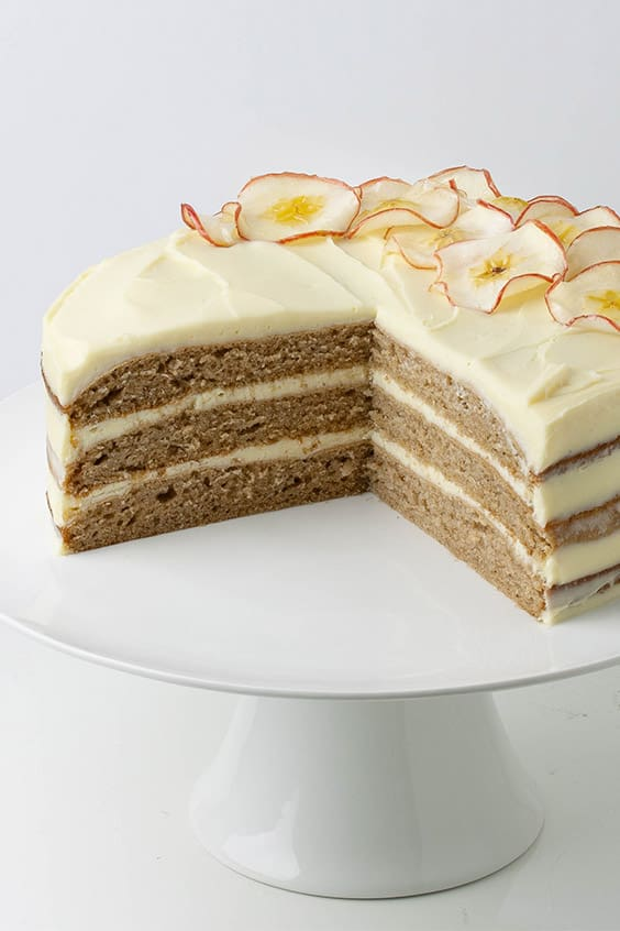 a triple layered cake, with a quarter cut out to show the inside, on a white cake stand with thick, pale yellow frosting decorative apple slices on one side of the cake