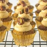A close up of cupcakes in golden foil cases on a wire rack
