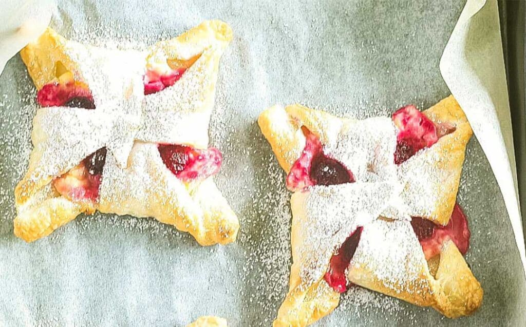 a close up image of two pastries with a raspberry cheesecake filling dusted with icing sugar