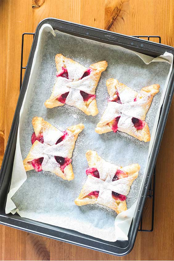 a baking tray with four icing sugar dusted raspberry cheesecake pastries
