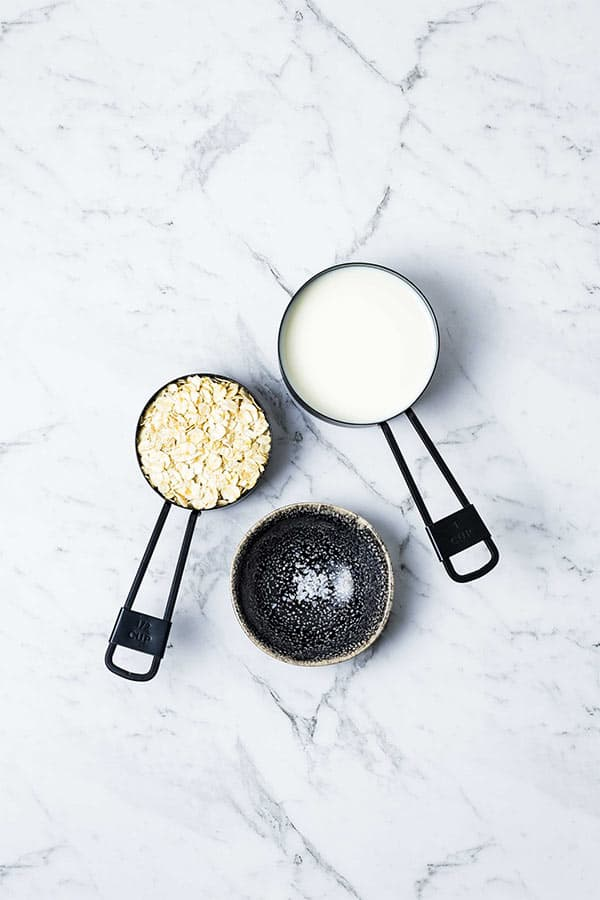 measuring cups with oats, milk and a small black dish with a pinch of salt