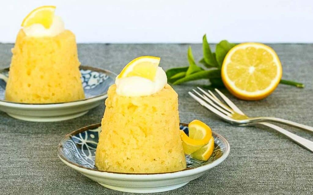 two individual steamed lemon puddings garnished with cream and lemon with dessert fork and a halved lemon on a dark surface