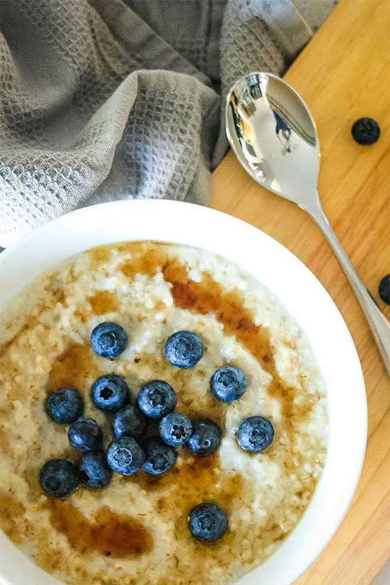 a blueberry and syrup topped bowl of steel cut oatmeal