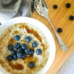 a bowl filled with steel cut porridge with syrup and blueberries on a wooden board