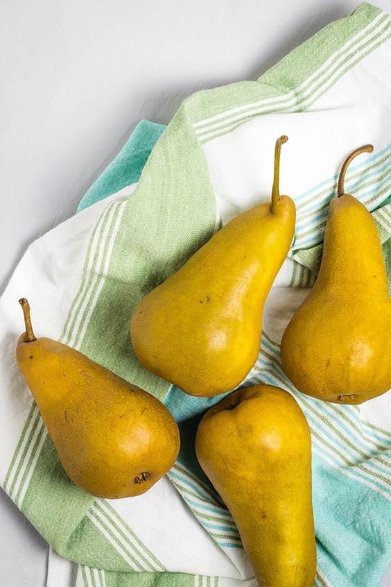 four ripe pears laid on a striped tea towel
