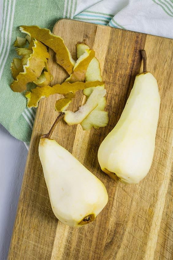 two pears on a wooden cutting board with the skin peeled off and lying beside them