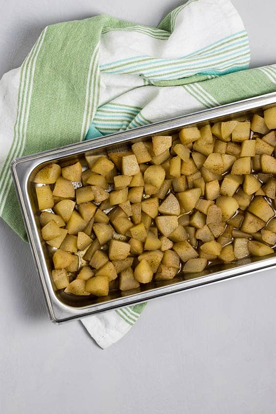 stewed diced fruit in a baking tin on a striped tea towel