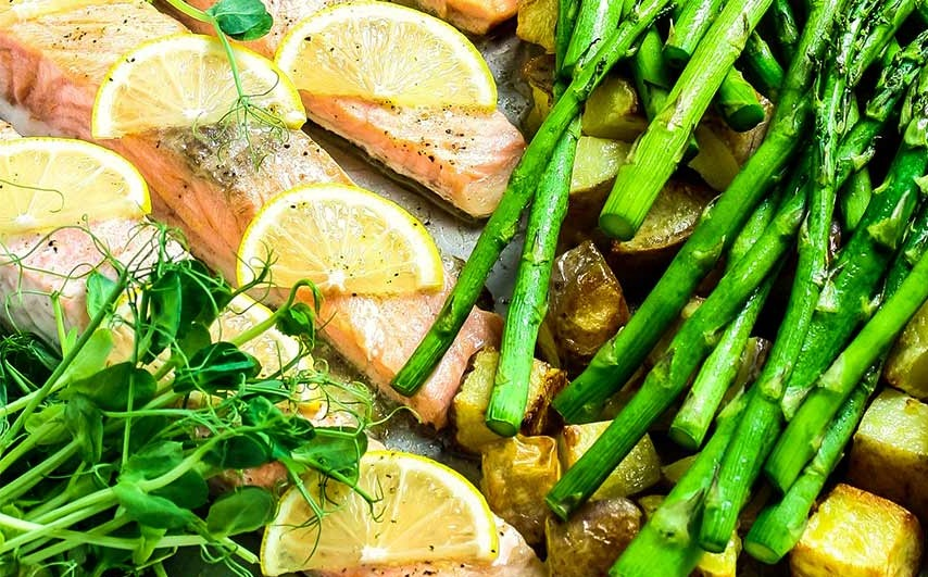 steam oven salmon fillets with lemon slices; asparagus and diced potatoes to the side