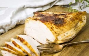 a turkey breast on a wooden chopping board with slices carved off one end and a serving fork resting beside it