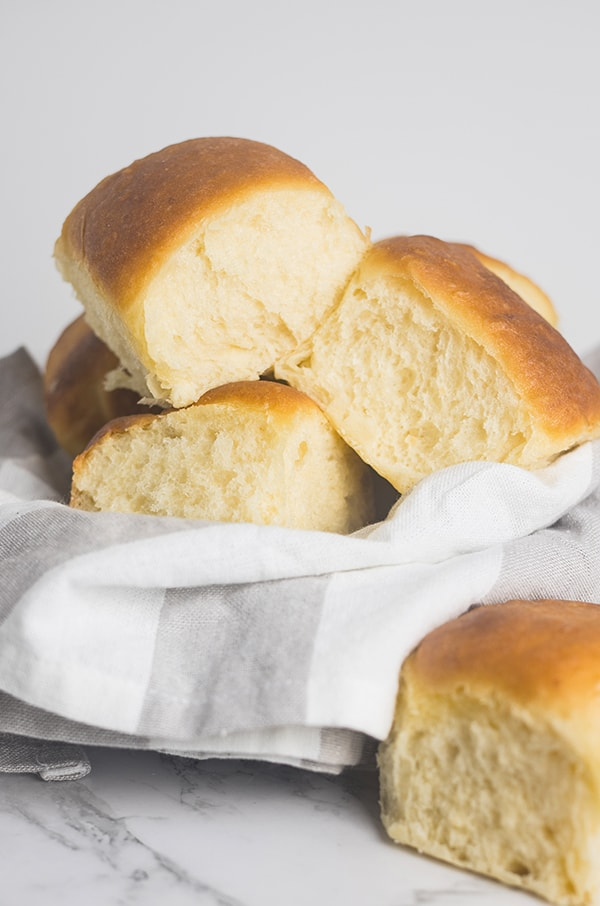 soft and fluffy potato rolls in a basket lined with a kitchen towel