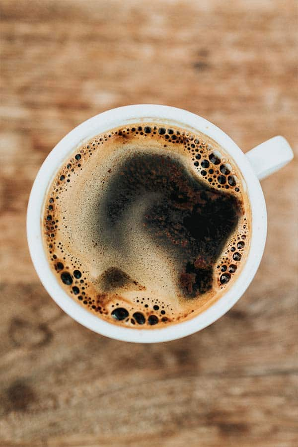 an overhead image of a cup of black coffee