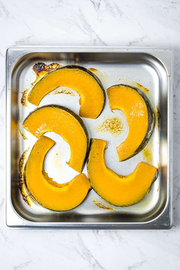 a square pan containing wedges of steam oven roasted pumpkin