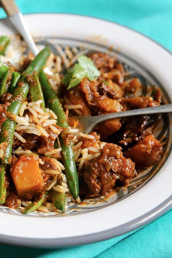 a plate of cooked meat in a brown sauce, cooked rice and steamed green beans