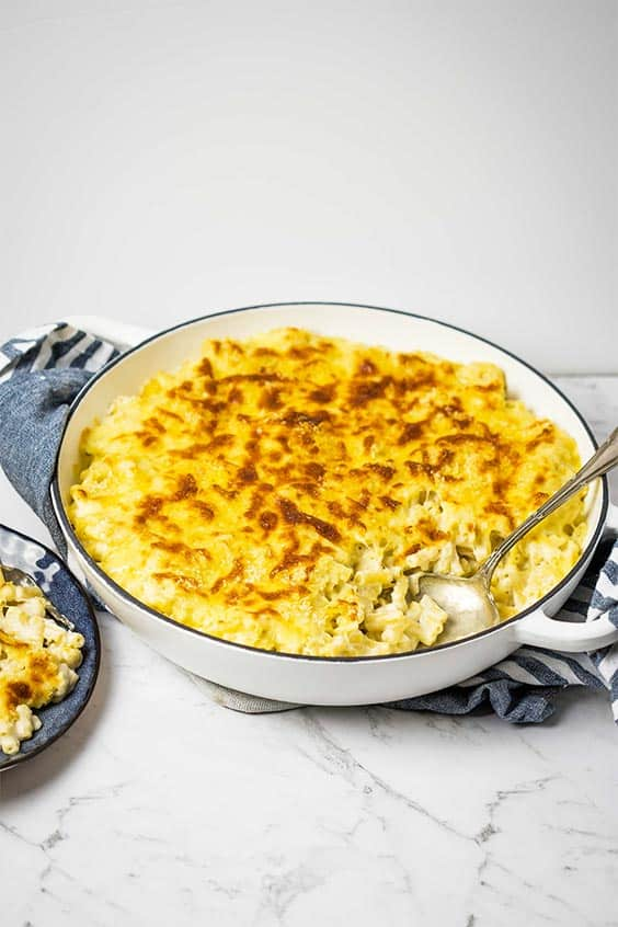 a round cream baking dish sitting on a blue kitchen cloth; baked mac and cheese is in the dish with a spoonful removed