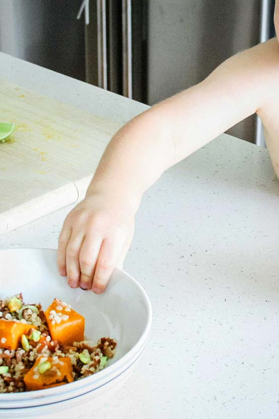 a child's hand grabbing a bowl of pumpkin and red rice salad