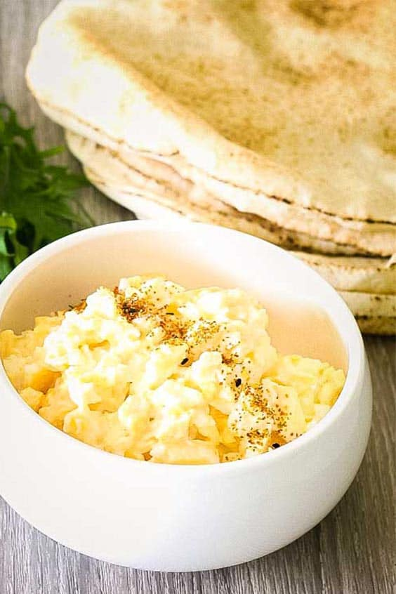 a white bowl full of scrambled eggs with a stack of flat breads in the background