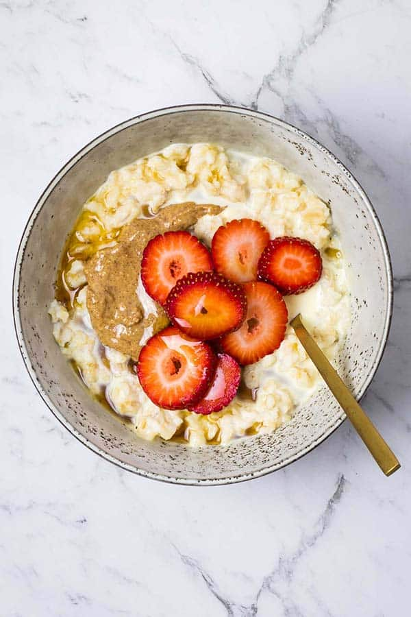 steam oven oatmeal topped with sliced strawberries and almond butter