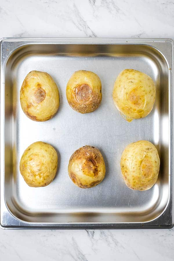 a square stainless steel pan with six roasted potatoes in it