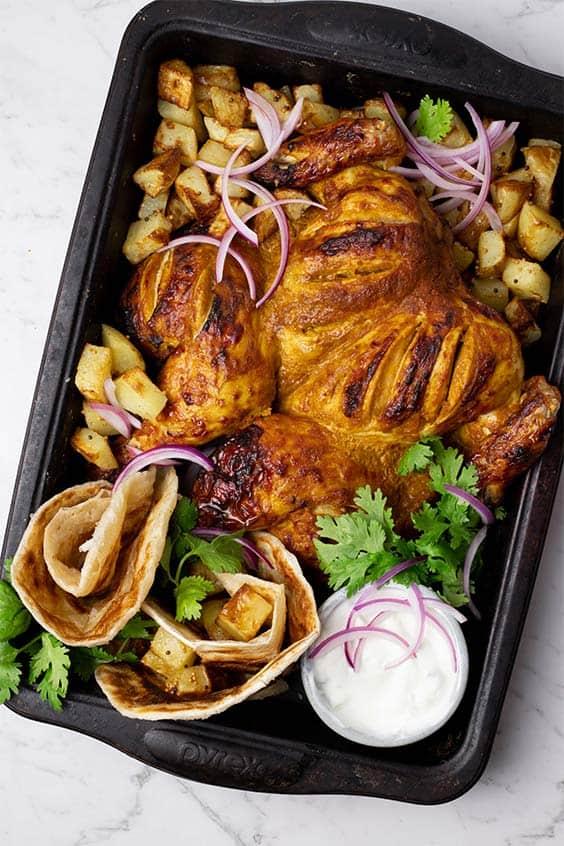 tandoori roasted butterflied chicken with roast potatoes and flatbread