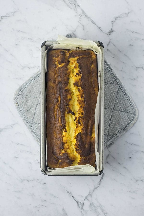 a golden loaf cake in a lined baking tin on a grey oven mitt