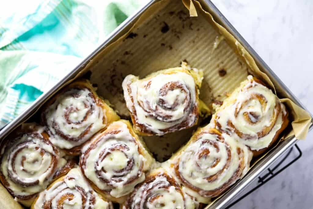 a steel tray containing glazed overnight cinnamon rolls with some missing from one end