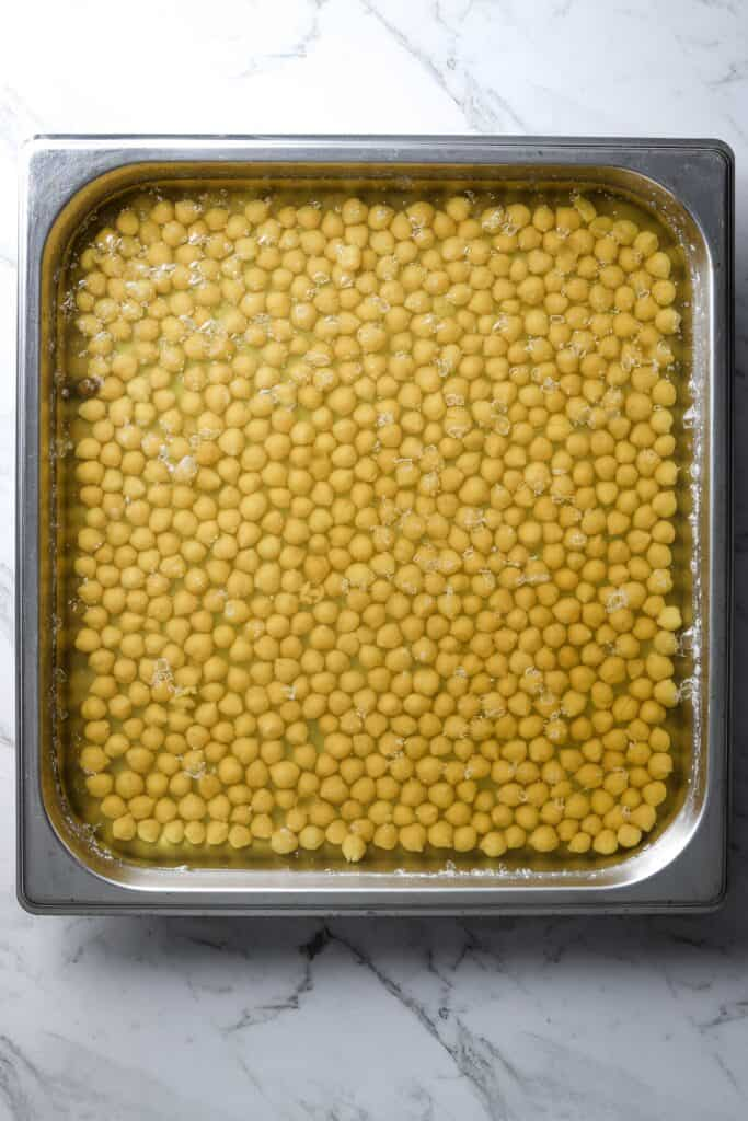 cooked chickpeas in a square baking tray