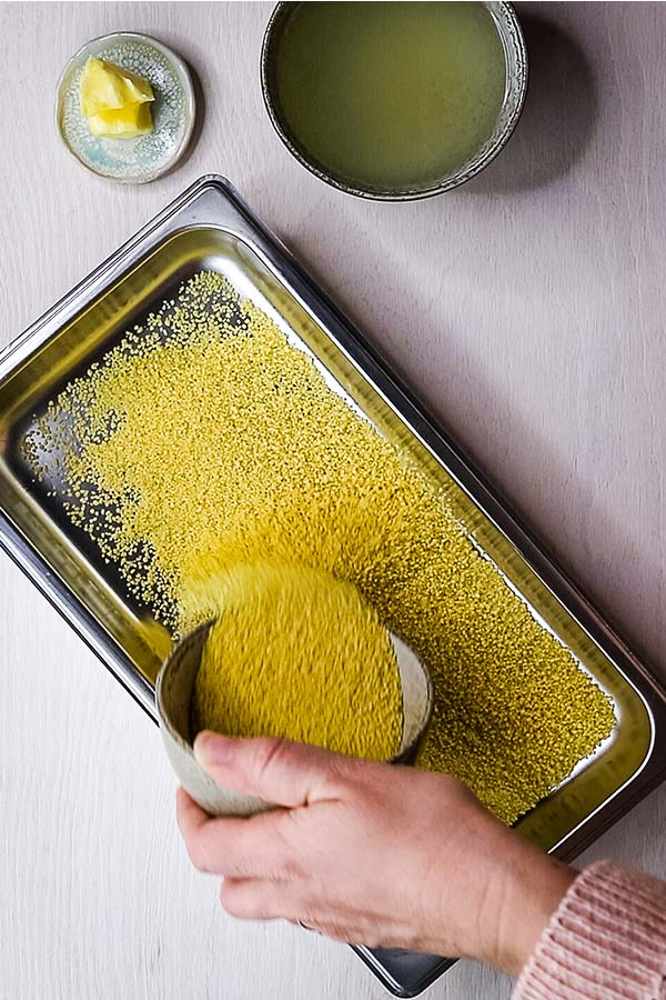 dry couscous being poured into pan