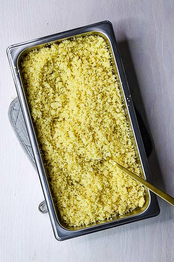 a rectangular metal pan of cooked couscous